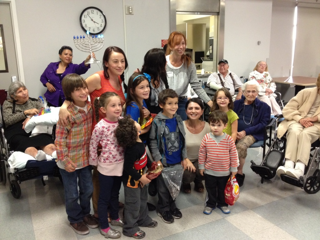Kid volunteers and their mothers after they sing Hanukkah songs to residents of Reseda's Jewish Home.