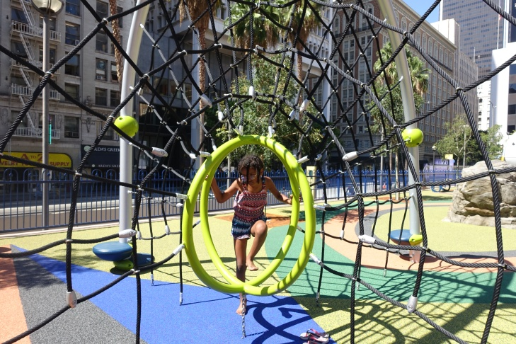 Zoe Ha takes a break from the swing at a new playground at Pershing Square.