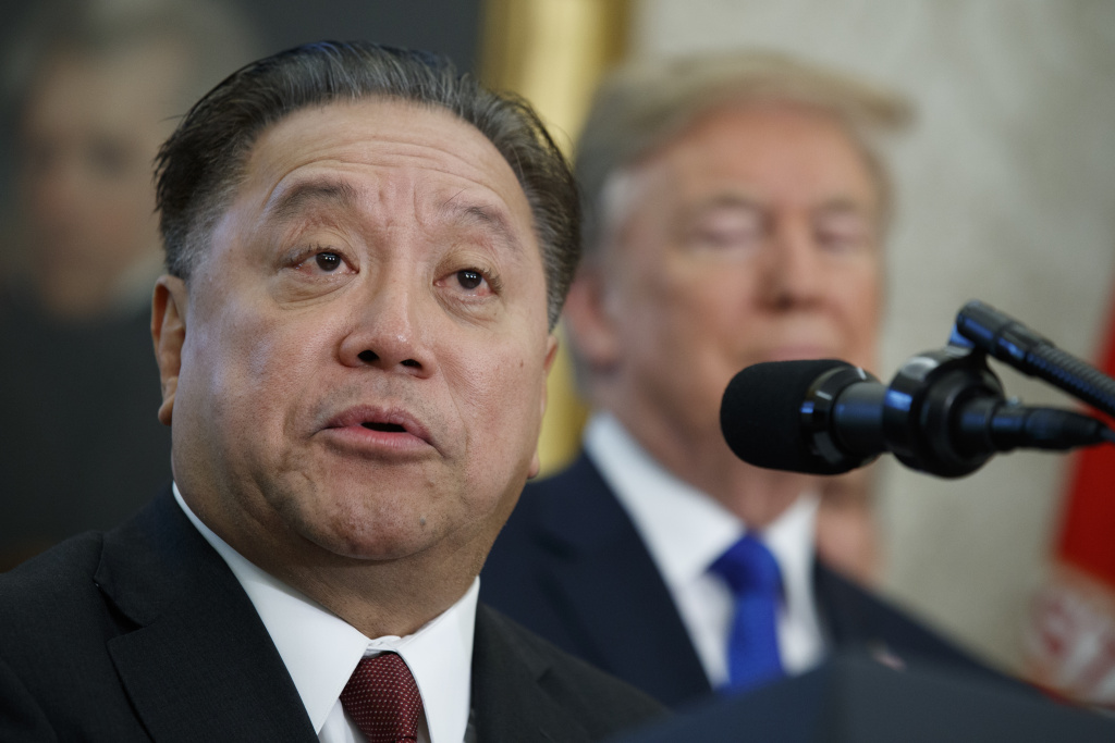 In this Thursday, Nov. 2, 2017, file photo, Broadcom CEO Hock Tan speaks as President Donald Trump listens during an event to announce the company is moving its global headquarters to the United States, in the Oval Office of the White House, in Washington. Broadcom is making an unsolicited, $130 billion offer for rival chipmaker Qualcomm.