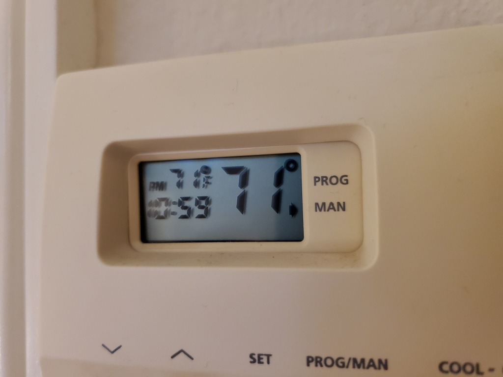 A wall-mounted thermostat in a California home. New research finds households that can least afford it are spending more than they have to on electricity.