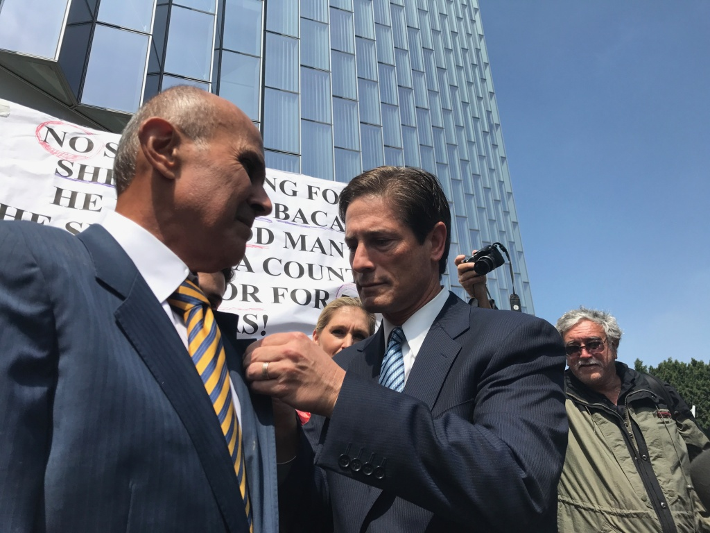Defense attorney Nathan Hochman, right, pins a sheriff's star to the lapel of ex-Los Angeles County Sheriff Lee Baca. Baca was sentenced to three years in prison on Friday.