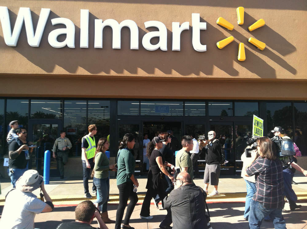 Photographers follow protesters marching in front of the Walmart in Paramount on Black Friday.