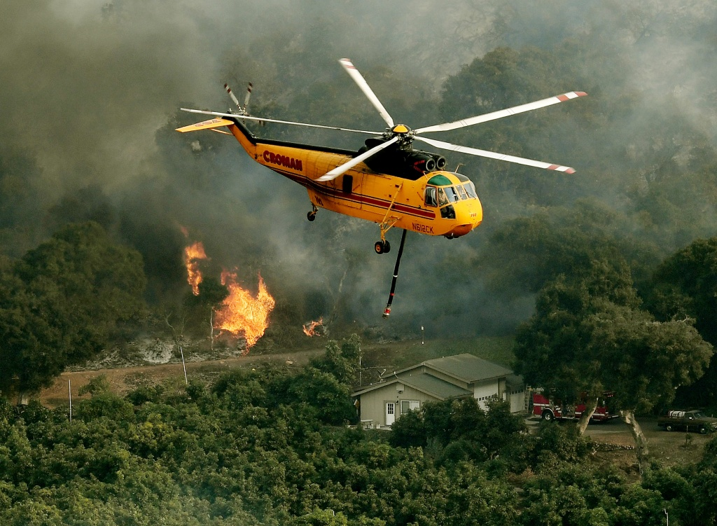 Firefighting helicopters try to save a house from the Thomas wildfire in 2017. After years of catastrophic fires, the state unveiled a new $536 million plan aimed at preventing such blazes.