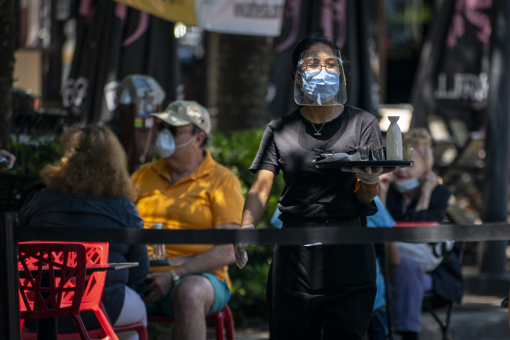 A waiter at Raku, an Asian restaurant in Bethesda, wears a protective face mask as serve customers outdoors amid the coronavirus pandemic on June 12, 2020 in Bethesda, Maryland.