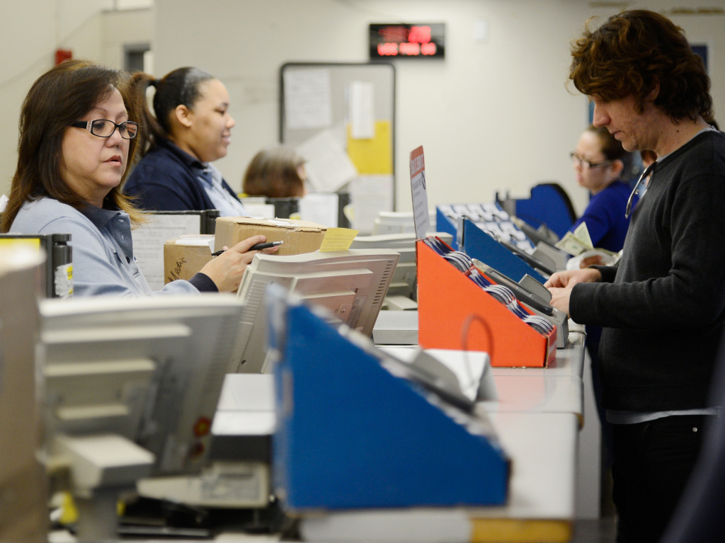 U.S. Postal Service clerks help customers at the Los Feliz Post Office in Los Angeles.
