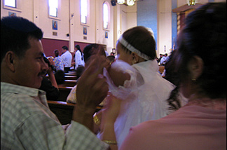 Hundreds of parents file into Our Lady Queen of the Angels Church to baptize their babies.