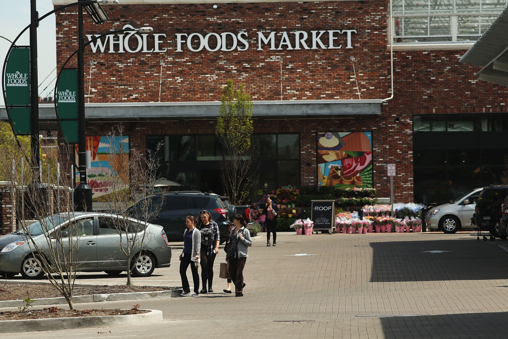 People walk out of Whole Foods Market in the Brooklyn borough on May 7, 2014 in New York City.