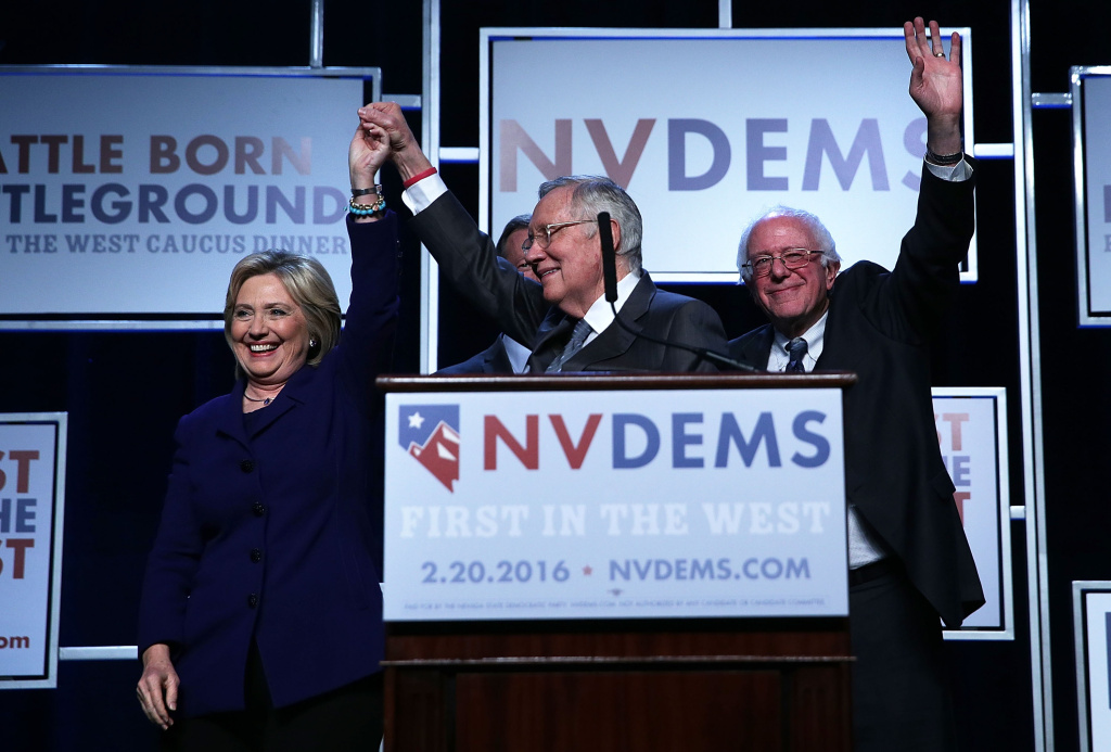 Democratic Presidential candidates Hillary Clinton (L) and Sen. Bernie Sanders (I-VT) (R) on stage with Senate Minority Leader Harry Reid (D-NV) (2nd L) prior to the Battle Born/Battleground First in the West Caucus Dinner at the MGM Grand in Las Vegas, Nevada.