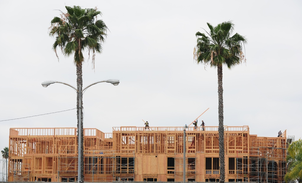 Construction workers are seen atop a builing of new apartments for sale in Alhambra, east of downtown Los Angeles on March 23, 2012 in California.