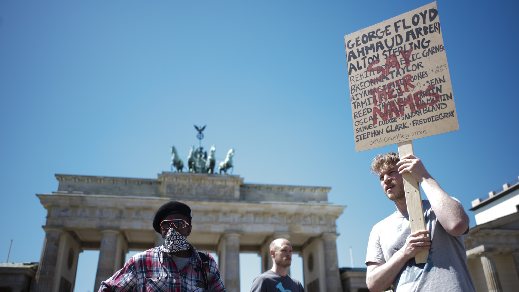 People attend a rally in front of the Brandenburg Gate in Berlin on Monday to commemorate George Floyd and protest against racism and police violence.