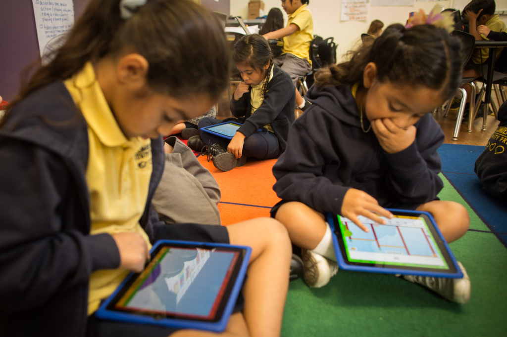 Second graders Lalia G., Ericka B. and Elisha G. use iPads for instruction at Komienza Community Prep in Huntington Park.