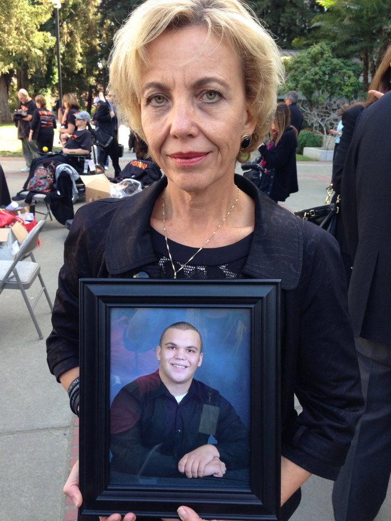 Tammy Smick holds a photograph of her son, Alexander, who died February 23, 2012 of an overdose. Smick told lawmakers the doctor who prescribed the lethal drugs practices medicine in Long Beach.
