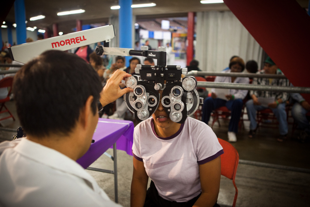 An optometrist performs an eye exam on a patient at CareNow's free clinic in the Los Angeles Sports Arena last year. Organizers have promised more dental and vision care for this September's free clinic.