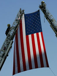 File photo: Firefighters hang an American flag over the route of the funeral procession for fallen Los Angeles Police Department (LAPD) SWAT Officer Randal Simmons, the first LAPD Swat officer ever killed in the line of duty in the 41-year history of the special operations team, on February 15, 2008 in Los Angeles, California.