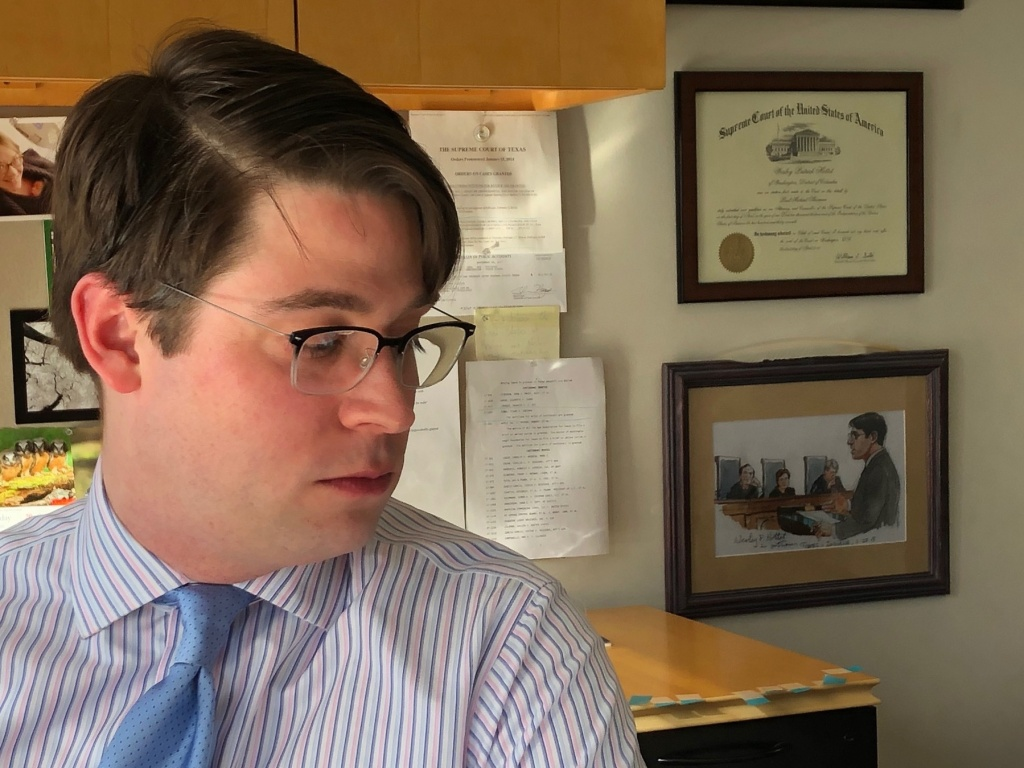 Institute for Justice lawyer Wesley Hottot in his Seattle office. On the wall is a framed illustration of him arguing Timbs v. Indiana at the Supreme Court last fall.