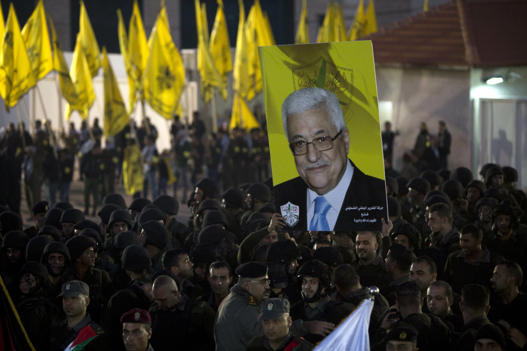 Palestinians hold up a poster showing President Mahmoud Abbas, as they celebrate the 50th anniversary of the Fatah movement in the West Bank city of Ramallah, Wednesday, Dec. 31, 2014. Palestinian President Mahmoud Abbas said the Palestinians will join the International Criminal Court, a move that sets the stage for filing a war crimes case against Israel. Abbas made the announcement in the West Bank on Wednesday, a day after the U.N. Security Council failed to pass a resolution that had aimed to set a deadline for Israel to end its occupation of territories sought by the Palestinians.