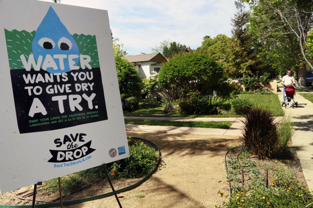 A sign encouraging people to save water is displayed at a news conference in Los Angeles. Two new bills will help Californians save water even during wet times.