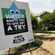 "A sign encouraging people to save water is displayed at a news conference in Los Angeles. Water use restrictions in California amidst the state's ongoing drought have led to the phenomenon of ""droughtshaming,"" or publicly calling out water wasters."