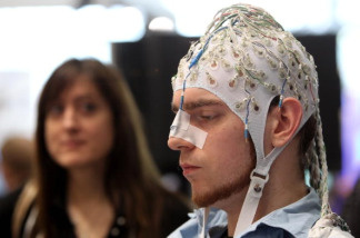 A young woman watches a man, wearing an EEG brain scanning apparatus on his head, play a pinball game solely through willing the paddles to react with his brain at the Berlin Brain Computer Interface research consortium stand at the CeBIT Technology Fair on March 2, 2010 in Hannover, Germany. CeBIT will be open to the public from March 2 through March 6.