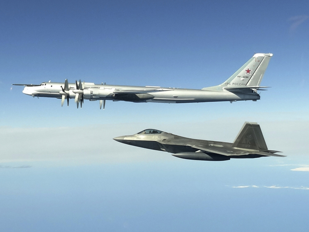 In this image taken June 16, 2020, and released by the North American Aerospace Defense Command, a Russian Tu-95 bomber (top) is intercepted by a U.S. F-22 Raptor fighter off the coast of Alaska. Russian nuclear-capable strategic bombers have flown near Alaska on a mission demonstrating the military's long-range strike capability.