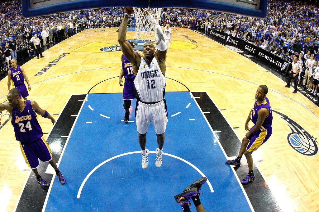 Dwight Howard #12 of the Orlando Magic slam dunks over Kobe Bryant #24 and Trevor Ariza #3 of the Los Angeles Lakers in Game Three of the 2009 NBA Finals on June 9, 2009 at Amway Arena in Orlando, Florida.