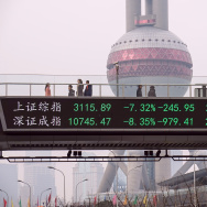 People walks along a pedestrian bridge with a screen showing stock market movements in Shanghai on January 7, 2016.