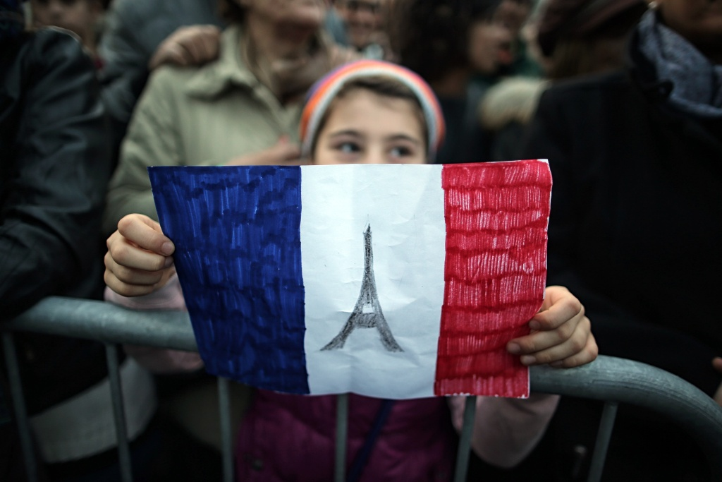 A child holds-up a hand drawn French flag as people gather on November 14, 2015 in Turin, a day after deadly attacks in Paris. At least 128 people were killed in the Paris attacks on the evening of November 13, with 180 people injured, 80 of them seriously, police sources told.