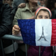 A child holds-up a hand drawn French flag as people gather on November 14, 2015 in Turin, a day after deadly attacks in Paris.