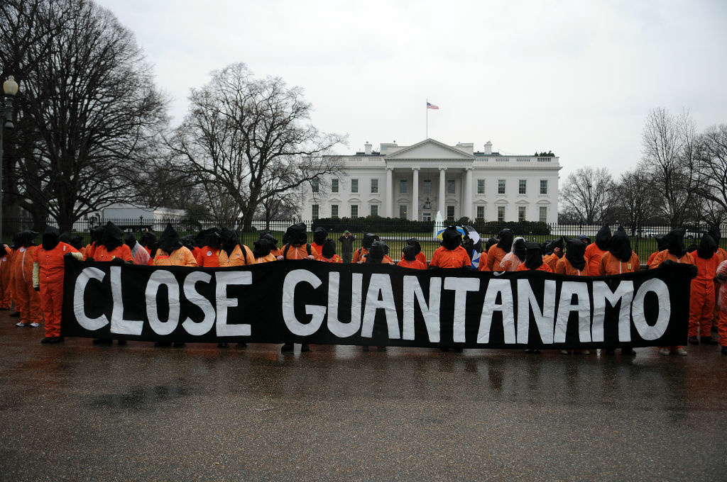 Members of the organization Witness Against Torture wear orange prison jump suits with handcuffs and a hood over their heads during a demonstration urging the government to close down the detention facility at Guantanamo Bay, in Lafayette Park outside the White House January 11, 2012 in Washington, DC. Protesters carry on a 92-hour vigil in a protest of the 10th anniversary of the arrival of the first group of detainees to arrive at the US military facility.