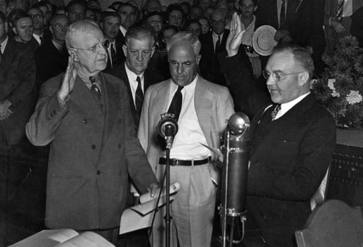 In a precedent setting ceremony, Judge Bowron is shown taking the oath of office in the City Council's chambers. This was the first time a mayor took office in a public ceremony and Bowron is the first mayor to be elected by means of a recall. Standing in front of the microphone from left to right: City Clerk Robert Dominguez, who is administering the oath; Council President Robert Burns, City Attorney Ray Chesebro, and Mayor Bowron.