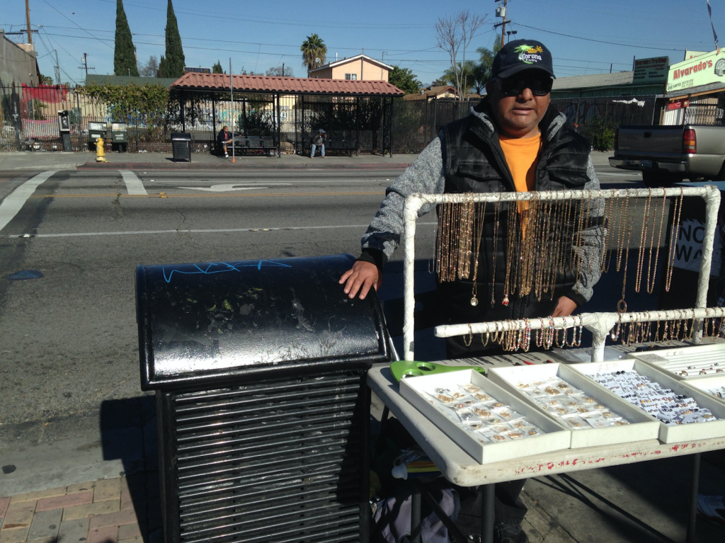 Armando Ventura sells gold-plated costume jewelry at the corner of Florence and Graham avenues in unincorporated Los Angeles County. He's one of several vendors cited recently. The city of Los Angeles is considering decriminalizing street vending, but the county is not.