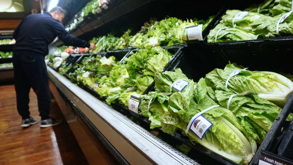 A man shops for vegetables near romaine lettuce for sale at a supermarket in California, where the first death from the <em>E. coli</em> outbreak was reported.