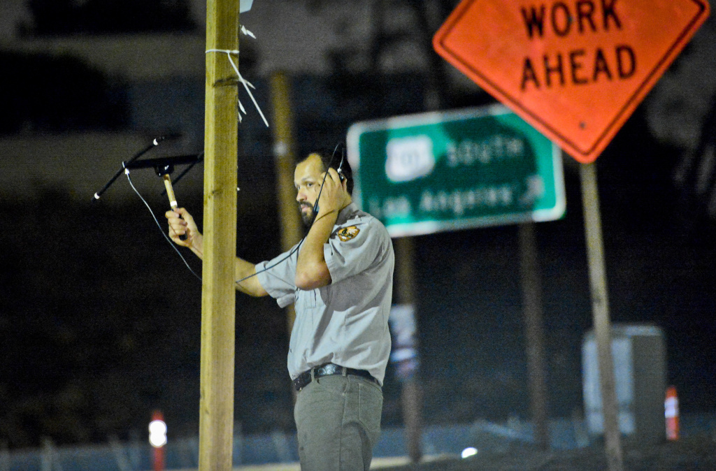 National Park Service ecologist Justin Brown uses a handheld antenna and scanner near the 101 freeway to listen for signals from radio-collared coyotes living near downtown Los Angeles early Thursday morning, June 4, 2016.  National Park Service Ecologist Justin Brown tracks coyotes living near downtown Los Angeles late Wednesday night June 3 and early Thursday morning June 4, 2015, in Los Angeles, CA. Some of the coyotes are fitted with radio collars.