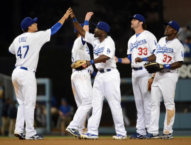 Tony Gwynn #10 of the Los Angeles Dodgers celebrates a 4-1 win over the Cincinnati Reds with Luis Cruz #47, Scott Van Slyke #33 and Elian Herrera #37 at Dodger Stadium on July 4, 2012 in Los Angeles, California.