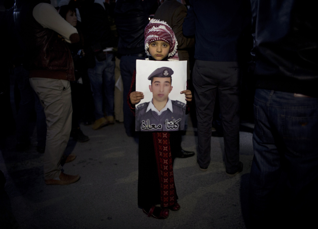 In this Monday, Feb. 2, 2015 file photo, a Jordanian child holds a poster with a picture of Jordanian pilot, Lt. Muath al-Kaseasbeh, who was being held by the Islamic State group militants. The Arabic reads,