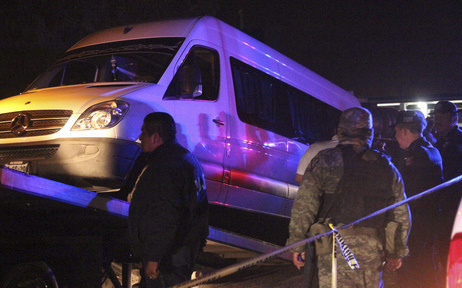 Police officers and soldiers stand around a white van containing the dead bodies of several man while it is being hauled onto a tow truck in San Luis Potosi on Thursday, August 9, 2012.