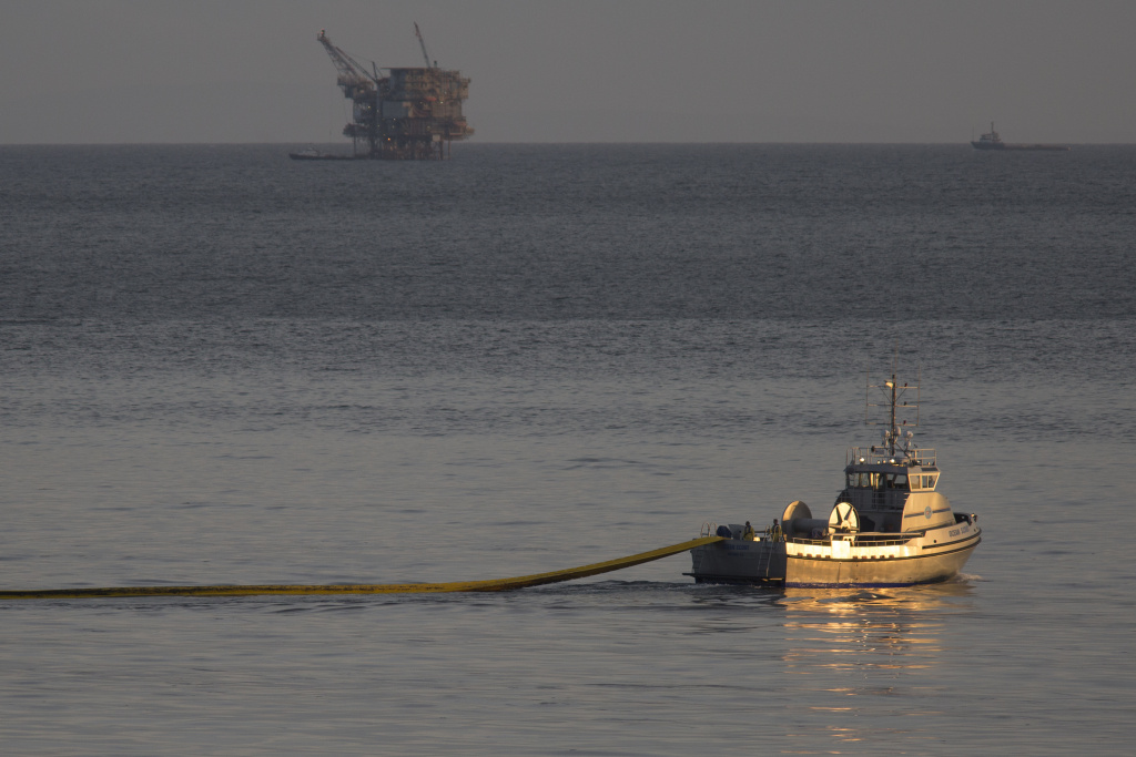 File: A boat with the nonprofit collective Clean Seas deploys a boom, with an oil platform seen in the distance, to try to contain an oil spill on May 19, 2015 north of Goleta, California.