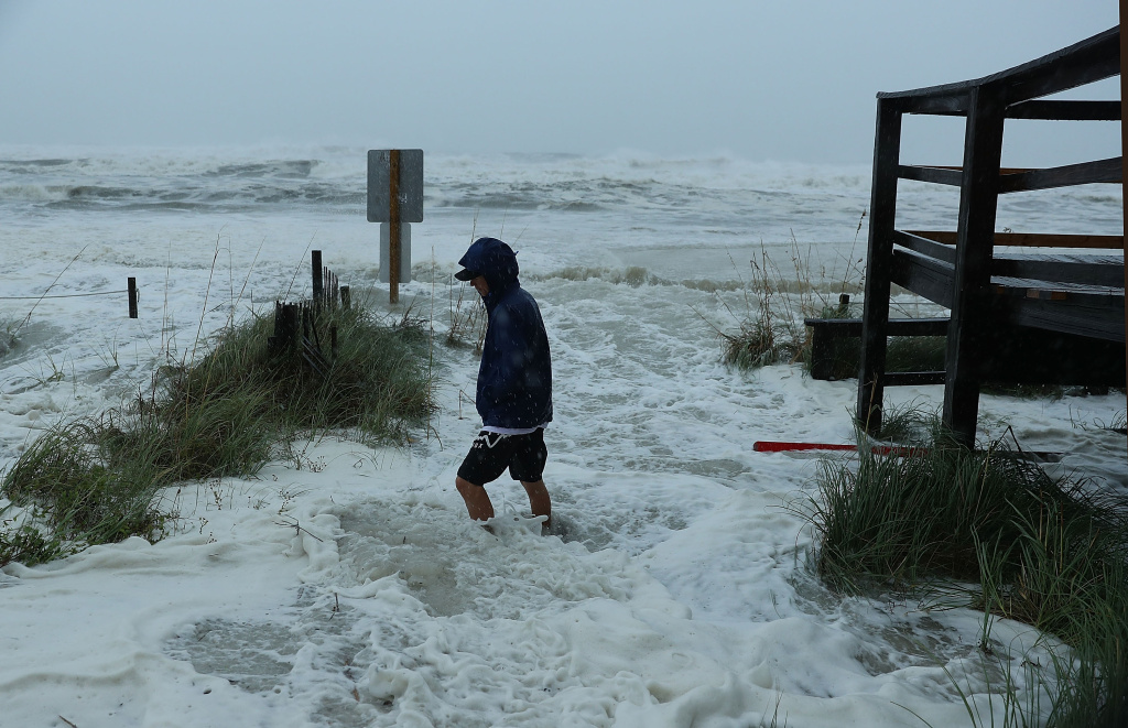 Cameron Sadowski walks along where waves are crashing onto the beach as the outer bands of  hurricane Michael arrive on October 10, 2018 in Panama City Beach, Florida.
