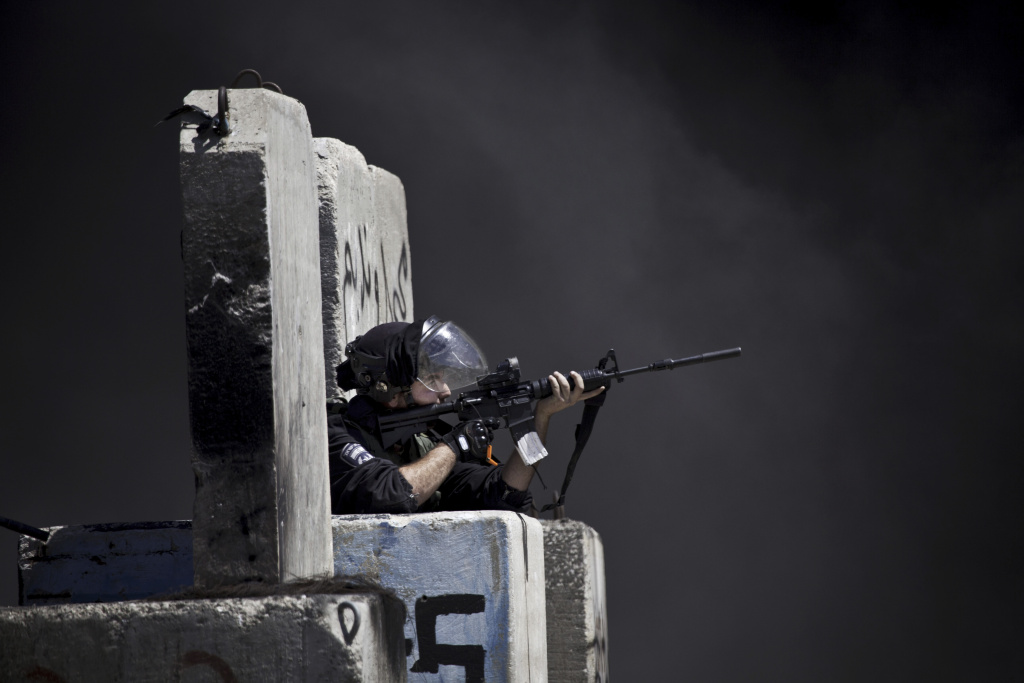 An Israeli border policeman aims his weapon during clashes with Palestinians following a protest against the Israeli offensive in Gaza, outside Ofer, an Israeli military prison near the West Bank city of Ramallah, Friday, July 18, 2014. Israeli troops pushed deeper into Gaza on Friday to destroy rocket launching sites and tunnels, firing volleys of tank shells and clashing with Palestinian fighters in a high-stakes ground offensive meant to weaken the enclave's Hamas rulers. (AP Photo/Majdi Mohammed)