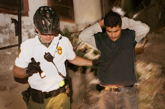 An U.S. Customs and Border Protection bike patrol agent apprehends an undocumented immigrant after he was spotted entering the country illegally June 2, 2010 in Nogales, Arizona.