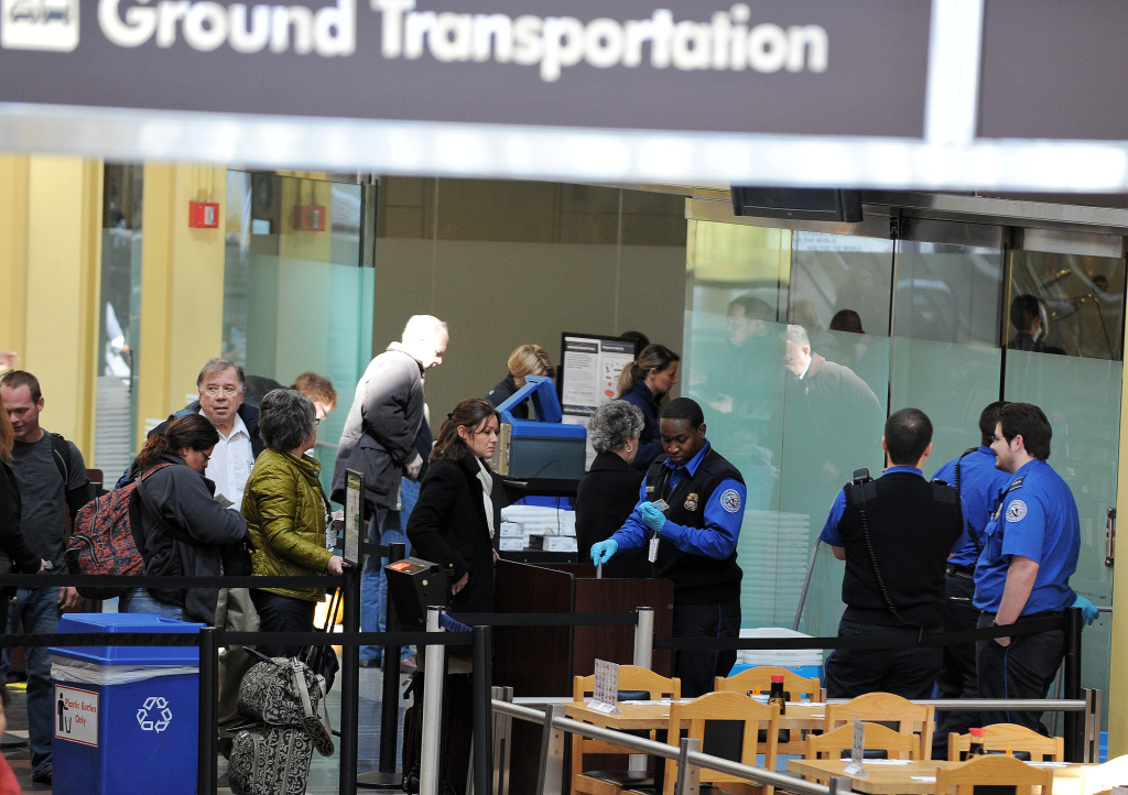 This file photo shows TSA officers checking carry-on luggage.