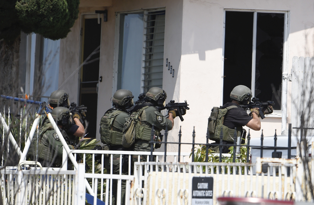 San Diego Police SWAT officers prepare to enter house with a possible suspect inside Friday, July 29, 2016, in San Diego. One San Diego police officer was killed and another was wounded in a shootout following a late-night traffic stop.