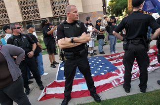 Policemen stand guard over a protesters' flag made by immigrant rights supporters as Arizona conservatives listen to speeches denouncing illegal immigration on July 31, 2010 in Phoenix, Arizona.