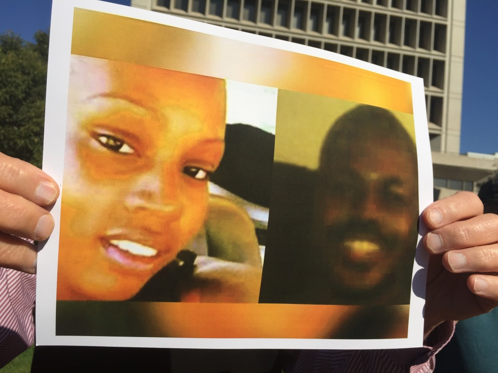 An activist holds up a pictures of Kisha Michael, left, and Marquintan Sandlin. Inglewood Police have yet to explain why they fatally shot the two in February. (11-02-16)