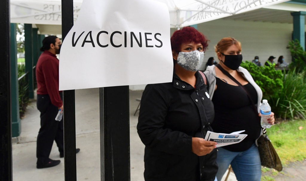 People arrive at a mobile Covid-19 vaccine site in Wilmington district of Los Angeles, California on April 13, 2021, where the Johnson & Johnson Covid-19 vaccine was due to be administered but changed to the Pfizer vaccine following a recommendation from federal health officials.