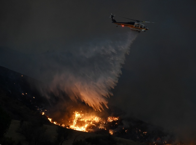 A hillside erupts in flame as a raging wildfire fire burns in Placerita Canyon in Santa Clarita, Calif., Monday, July 25, 2016. A raging wildfire that forced thousands from their homes on the edge of Los Angeles continued to burn out of control Monday as frustrated fire officials said residents reluctant to heed evacuation orders made conditions more dangerous and destructive for their neighbors.