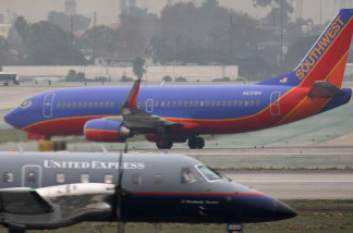 A Southwest airplane taxies as a United Express takes off at Los Angeles International Airport (LAX) after a snow storm on the East Coast caused the cancellation of numerous flights out of LAX over the weekend on December 21, 2009 in Los Angeles, California.