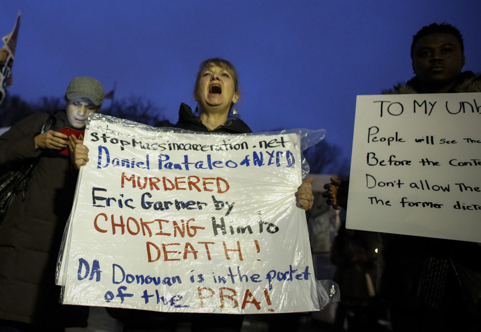 NEW YORK, NY - DECEMBER 3: A woman holds a banner as she takes part during a protest in support of Eric Garner at Union Square on December 3, 2014 in New York City. Garner died after being put in a chokehold during an alteration with NYPD officers in the Staten Island borough of New York City.  (Photo by Kena Betancur/Getty Images)