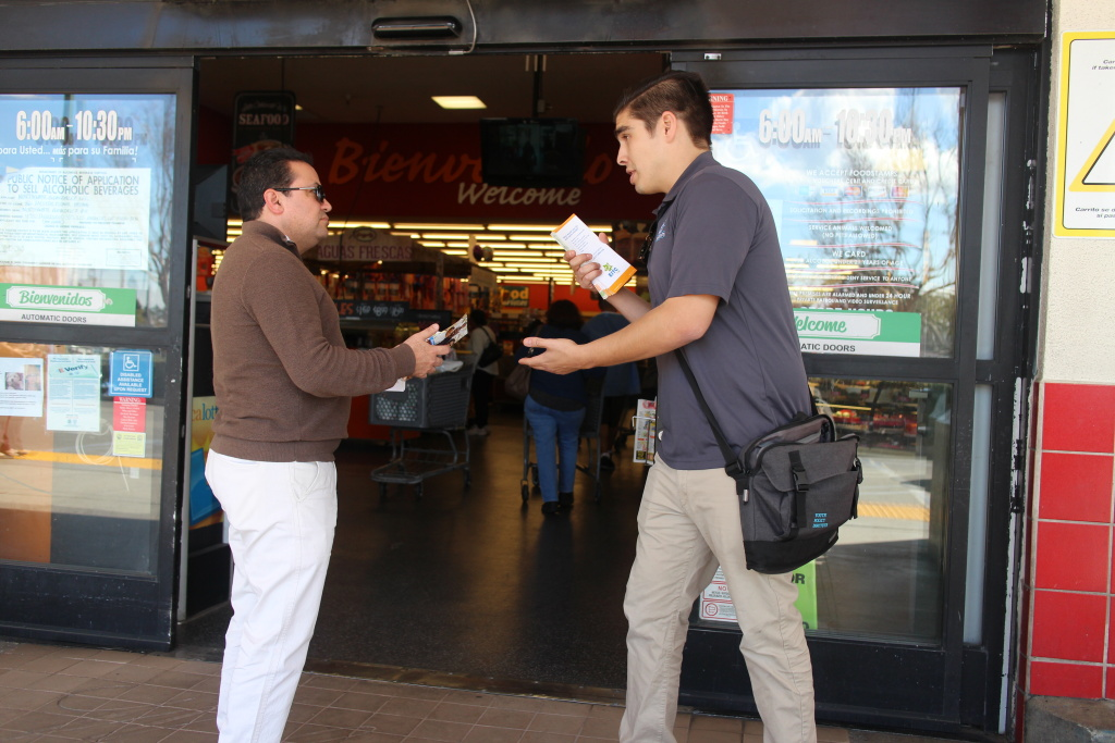 Matthew Fontana, a promotor with the Youth Policy Institute, talks with a shopper outside of the Northgate Market in Culver City.
