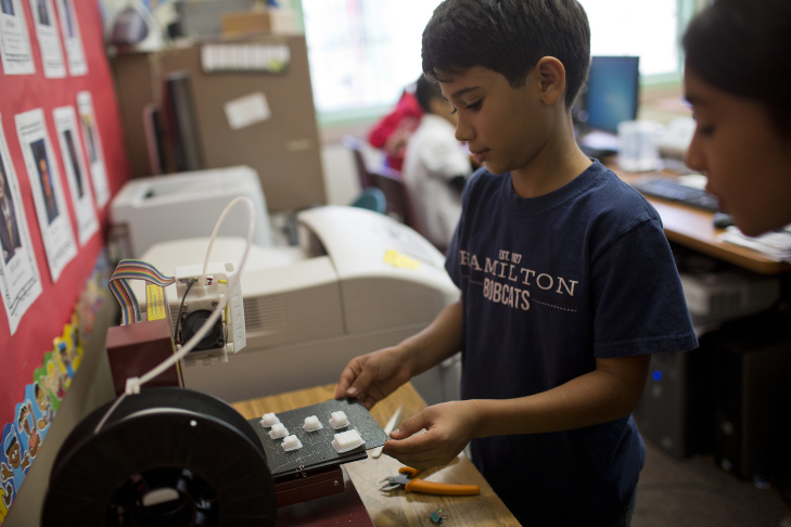 Fifth-grader Noah George removes a plate with finished pieces off a 3D printer in the Hamilton Elementary School computer lab on Jan. 13. Schools in the Pasadena Unified School District have began incorporating the printers into class curriculum.